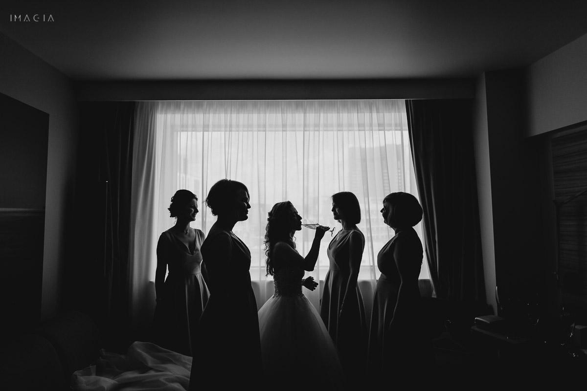 Mireasă îmbrăcând rochia de mireasă, împreună cu domnișoarele de onoare la o nuntă în București, la Hotel Novotel
