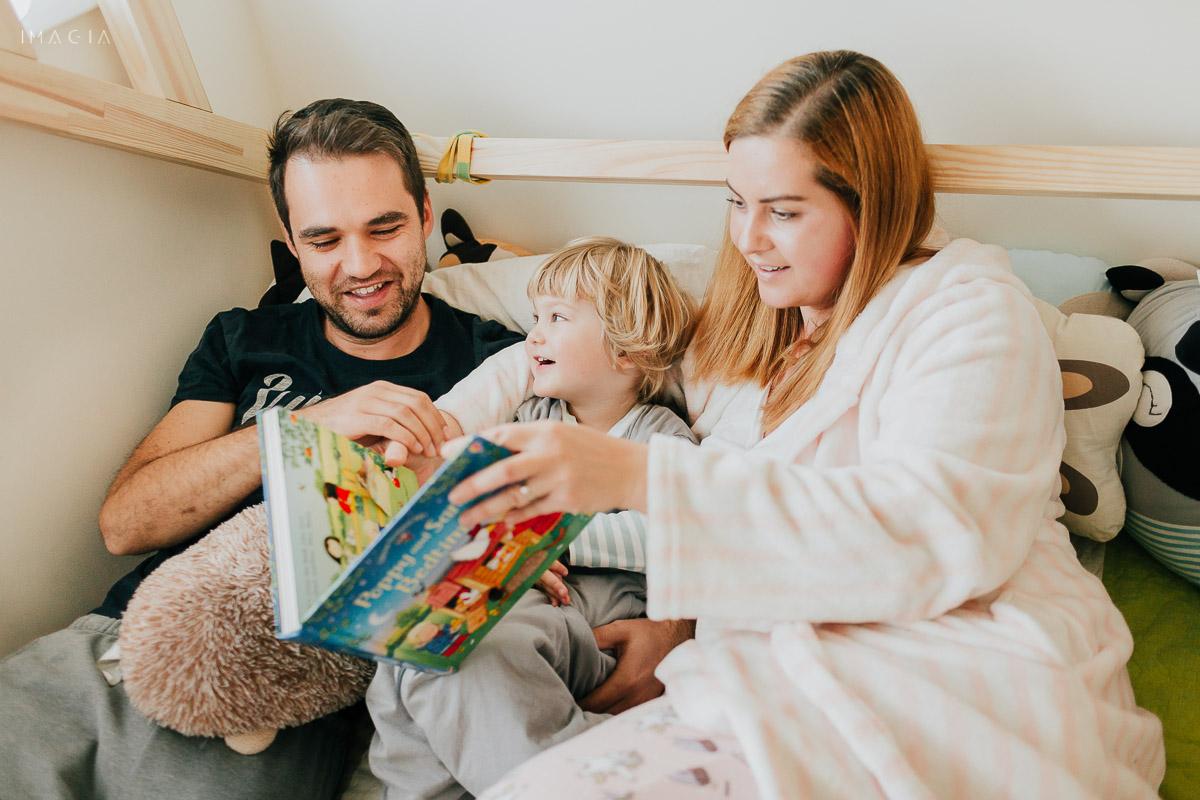 Părinți cu copilul ăn pat, citind povești