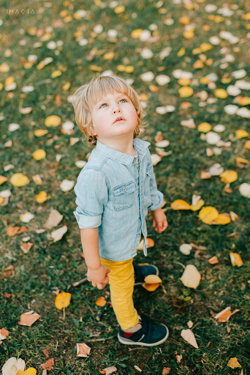 Copil printre frunze de toamnă